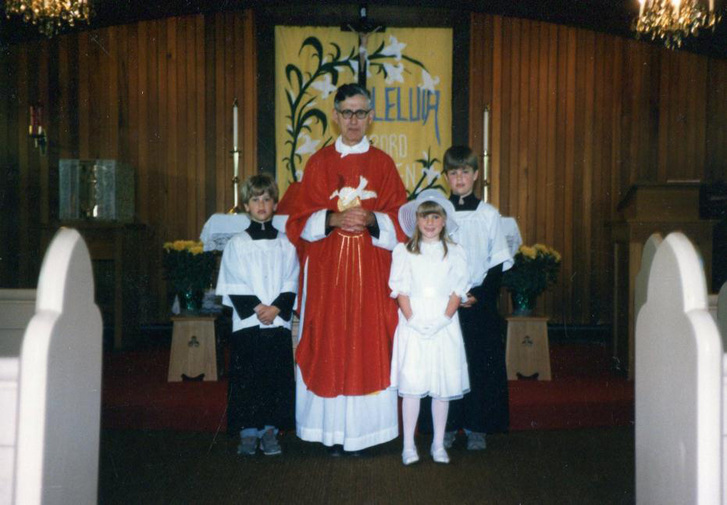 Celebration of the Eucharist with a female and male student and priest in the middle