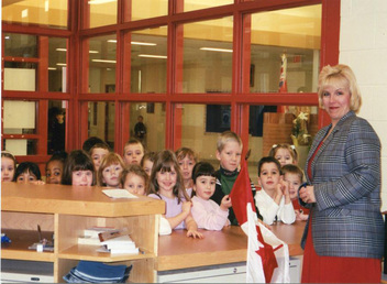 Adult female principal with Kindergarten students in school