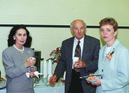 Two female and one male adult holding coffee and snacks