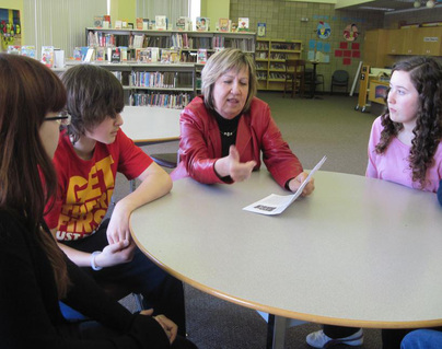 Female adult principal talking to Grade 8 students in library