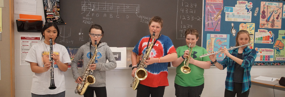 Students playing music instruments in a classroom